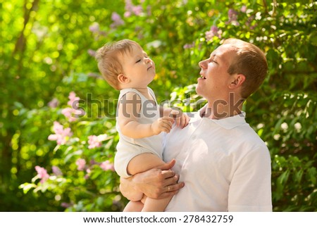 Father dad parent holding baby boy outdoors in summer garden, talking together