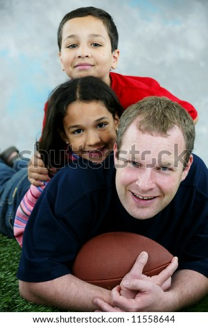 Father, daughter and son playing football - stock photo
