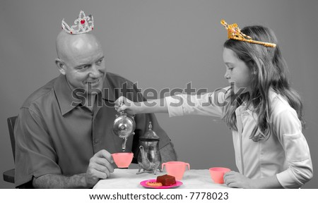 Father Dressed in Tiara Having Princess Tea Party with Daughter - stock photo
