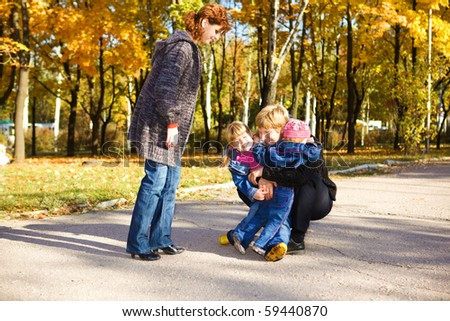 Father embracing daughters in autumn park
