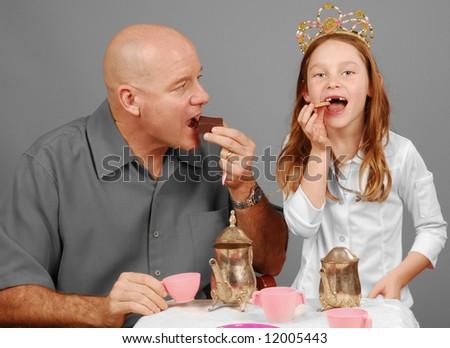 Father enjoying treats at tea party with princess daughter - stock photo