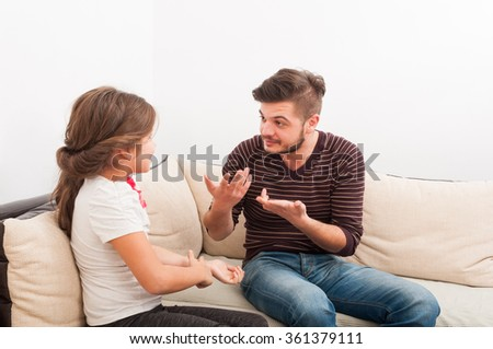 Father explaining or teaching young daughter in the living room on the sofa or couch - stock photo