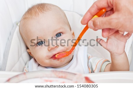 Father feeding baby boy with vegetables - stock photo