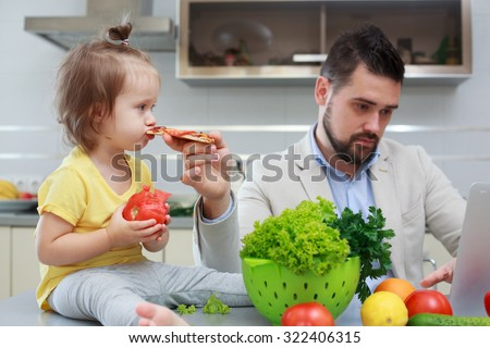 Father feeding fastfood baby during home work - stock photo