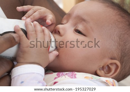 Father feeding her 3 months old baby girl with formula powder.  - stock photo