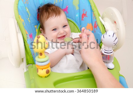 Father feeding his happy little cute baby - stock photo