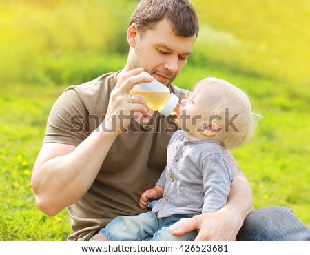 Father feeds baby from bottle on grass in summer day - stock photo