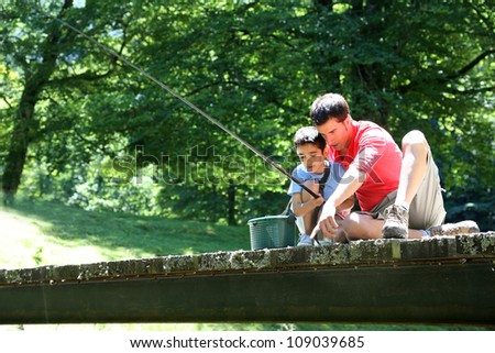 Father fishing with son on a bridge in the mountain - stock photo