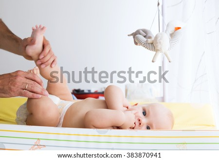 Father gently care of baby on the changing table at home - stock photo