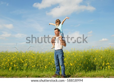 Father gives her daughter piggyback , windmills in the background
