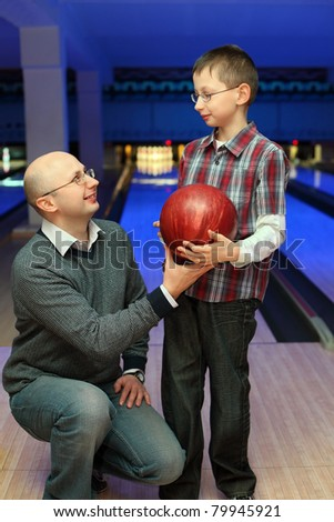 Father gives  son  red ball for bowling - stock photo