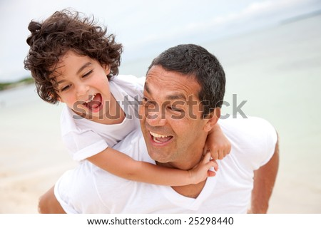 father giving a piggyback ride to his son - stock photo