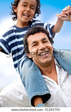 father giving a piggyback ride to his son - stock photo