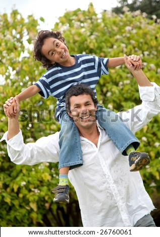 father giving a piggyback ride to his son outdoors - stock photo