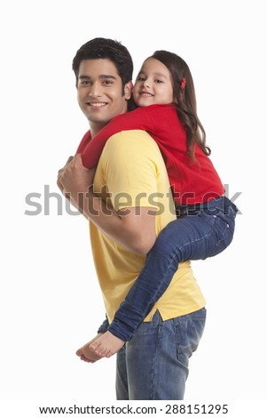 Father giving daughter piggy back ride - stock photo