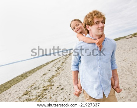 Father giving daughter piggy back ride at beach - stock photo