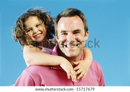 Father giving daughter piggyback ride outdoors smiling - stock photo