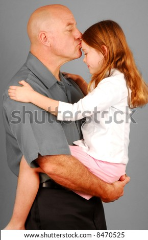 Father giving daughter sweet kiss on the forehead - stock photo