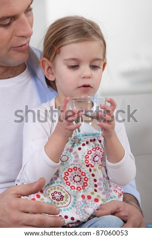 Father giving his daughter a glass of water to drink - stock photo