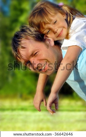 Father giving his lovely daughter piggyback - stock photo