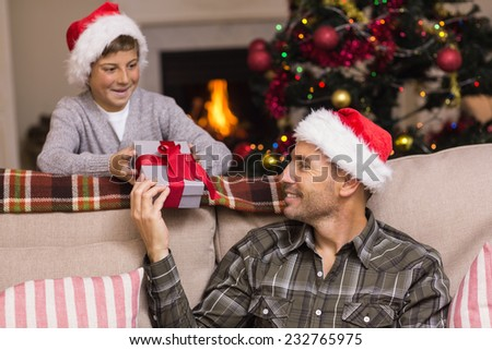 Father giving his son a christmas present at home in the living room - stock photo