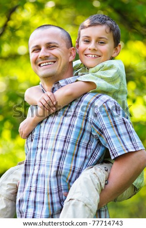 Father giving his son a piggyback ride, having fun