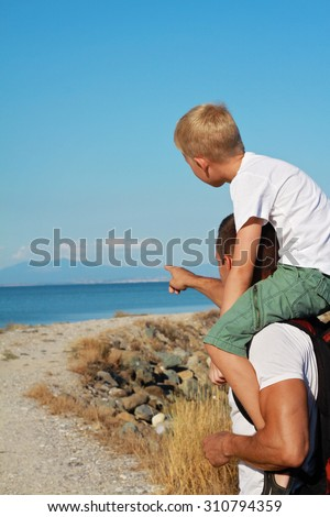 Father giving his son piggyback ride outdoors. Man and boy son in front of sea, pointing away, active summer holiday vacation, family travel photo - stock photo