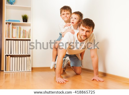 Father giving his two sons piggy back ride