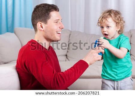 Father giving little son a bottle with drink