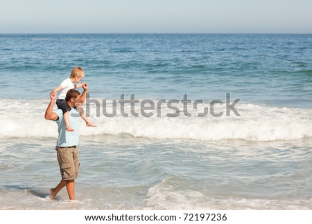 Father giving son a piggyback on the beach - stock photo