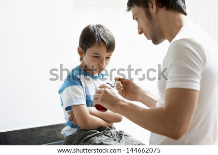 Father giving son cough syrup at home - stock photo