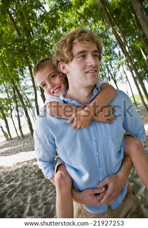 Father giving son piggy back ride - stock photo