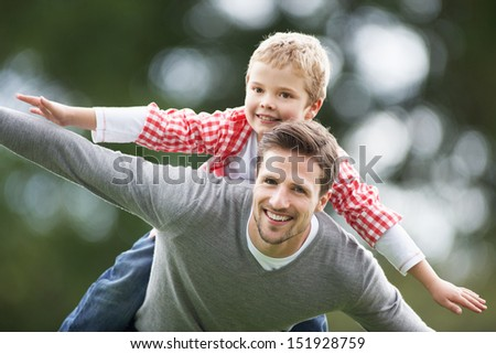 Father Giving Son Piggyback In Countryside - stock photo