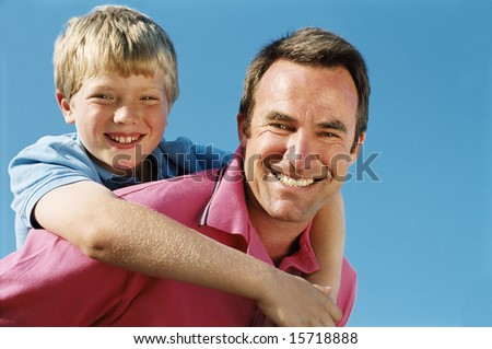 Father giving son piggyback ride outdoors smiling - stock photo