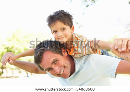 Father Giving Son Ride On Back In Park - stock photo