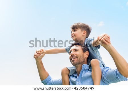 Father giving son ride on back in park. Portrait of happy father giving son piggyback ride on his shoulders and looking up. Cute boy with dad playing outdoor.