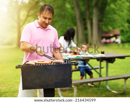 father grilling hot dogs and bratwurst for family at barbecue - stock photo