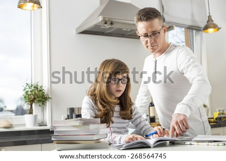 Father guiding daughter in doing homework at table - stock photo