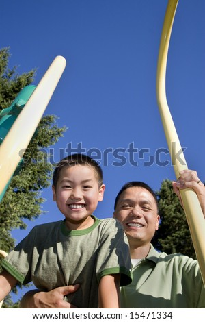 Father has arm around son and is holding fireman's pole with other hand. Both are looking down and smiling at camera. Vertically framed photo.