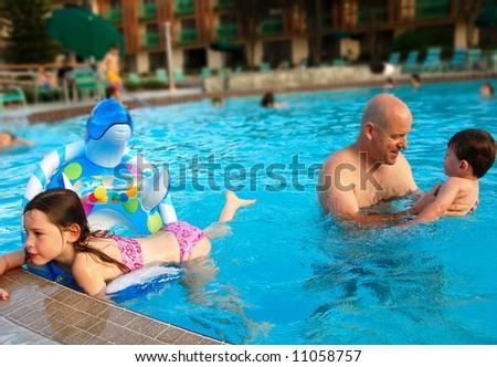 Father having fun with children in big swimming pool - stock photo