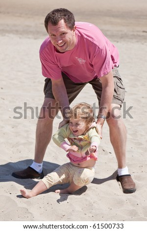 Father having fun with his daughter on the beach. - stock photo