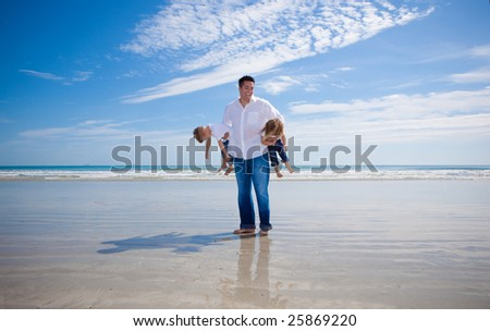 Father having fun with his kids on a beach. - stock photo