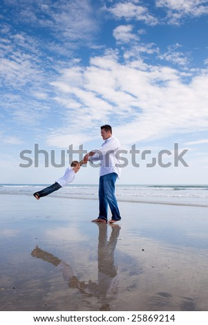Father having fun with his son on a beach. - stock photo