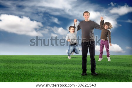 father having fun with his two children in a grass field - stock photo