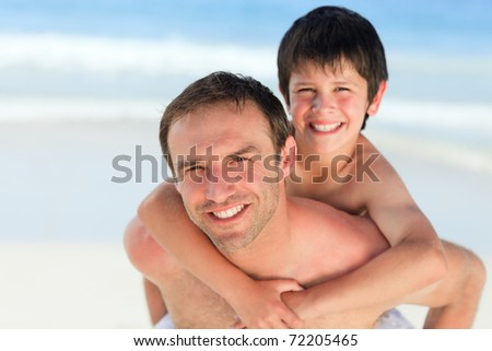 Father having son a piggyback on the beach