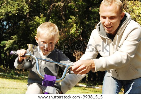 Father help his little son to riding by bicycle - stock photo