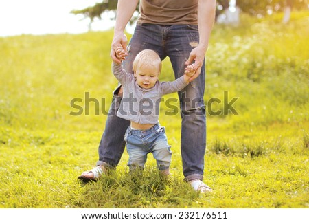 Father helping baby doing first steps in summer day - stock photo