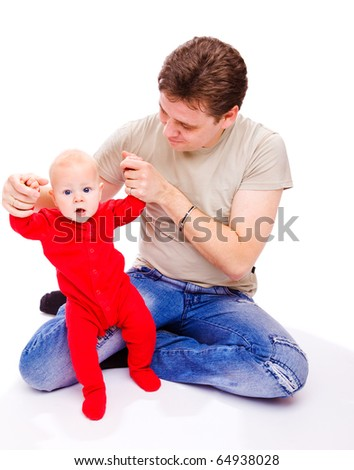 Father helping baby in red bodysuit to make his first steps - stock photo