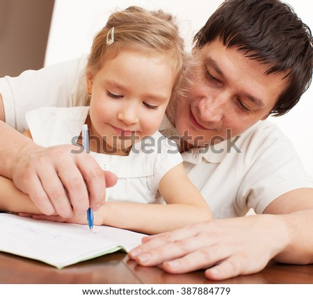 Father helping daughter doing homework. Parent with child writing - stock photo