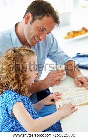Father Helping Daughter With Homework In Kitchen - stock photo